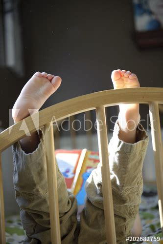 """""""Closeup little boy's feet on bed while he is reading"""