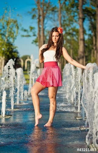 """""""teen girl wearing red skirt playing at outdoor water"""